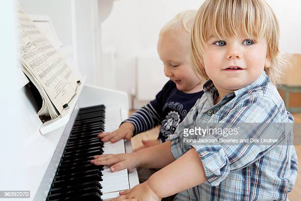 Two boy toddlers sitting at a piano