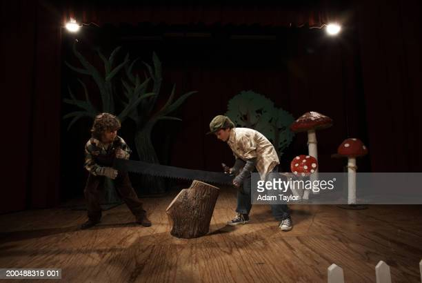 two boys (9-11) acting as lumberjacks on stage, sawing tree stump - acting performance stock pictures, royalty-free photos & images