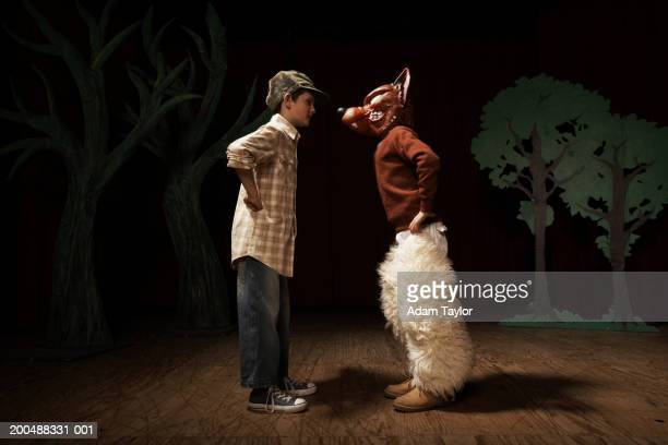 two boys (9-11) acting on stage, one boy confronting other as bad wolf - acting performance stock pictures, royalty-free photos & images