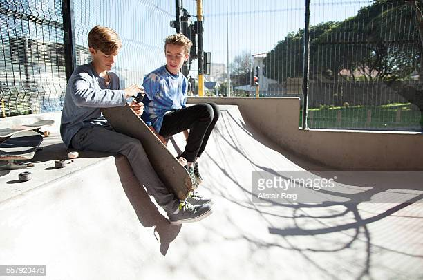 Two boys adjusting their skateboards