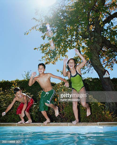 Two boys and a girl (7-13) jumping into swimming pool (blurred motion)
