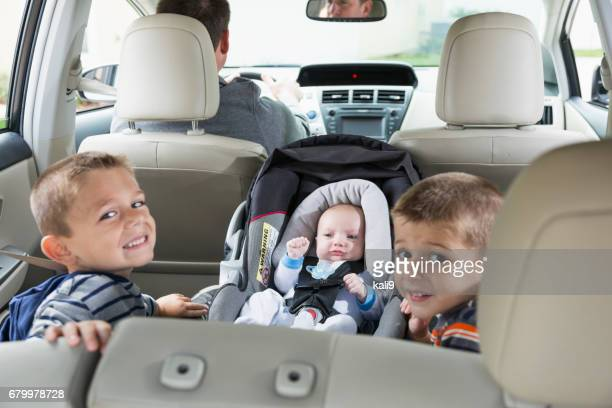 Two boys and baby in back seat of car, father driving