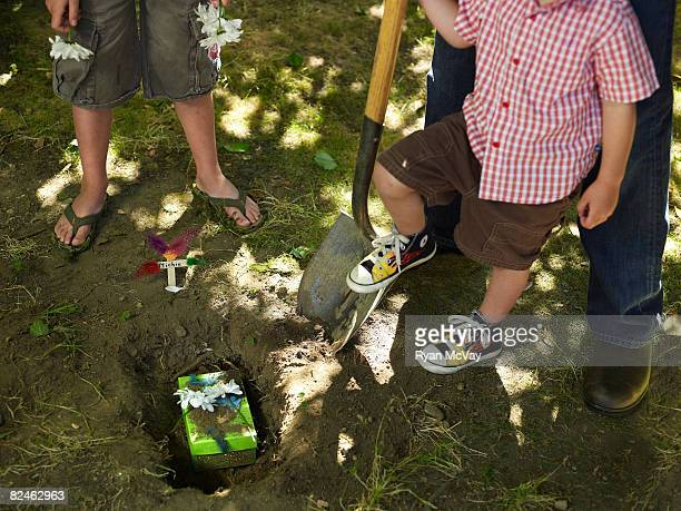 Two boys and man at pet graveside