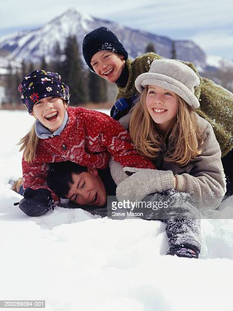 Two boys (14-15) and two girls (12-13) playing in snow