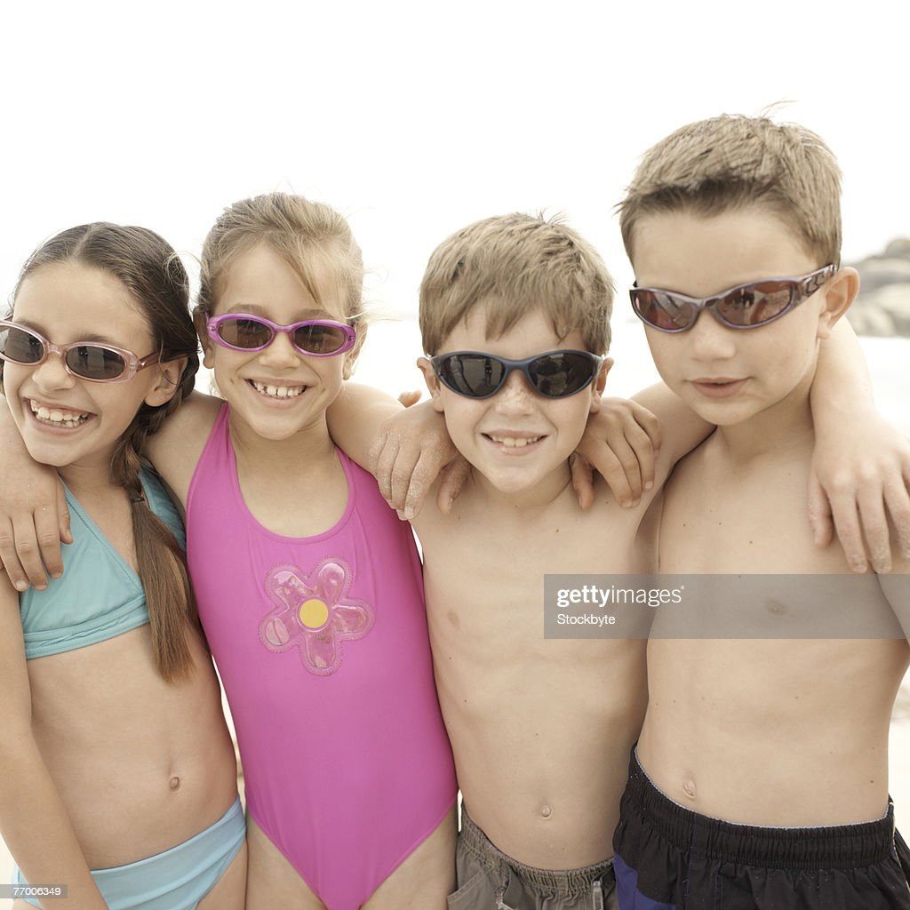 Two Boys And Two Girls Wearing Sunglasses On Beach
