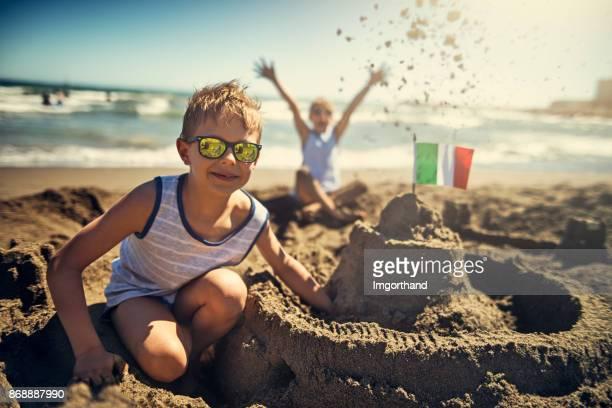 dos chicos están construyendo un castillo de arena en la playa italiana - bandera italiana fotografías e imágenes de stock
