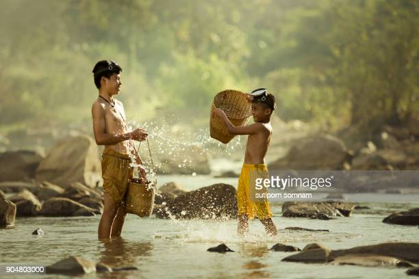 Two boys are playing splash in the stream.