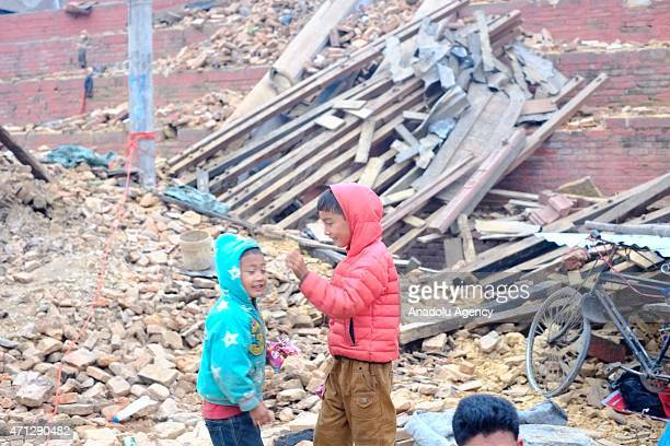 Two boys are seen among the debris of houses after a powerful earthquake hits Katmandu Nepal on April 26 2015 The death toll in Nepal climbed towards...