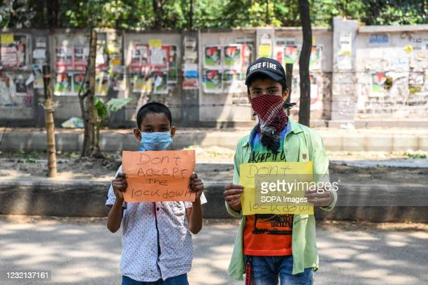 """Two boys are seen standing on a street while holding placards saying """"donít accept the lockdown"""" at Keraniganj."""