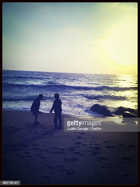 two boys at beach at sunset - carvajal ストックフォトと画像