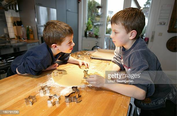 Two boys at the backing of Christmas cookies / biscuits