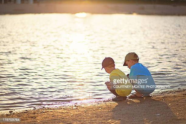 Two boys at the lake at sunset