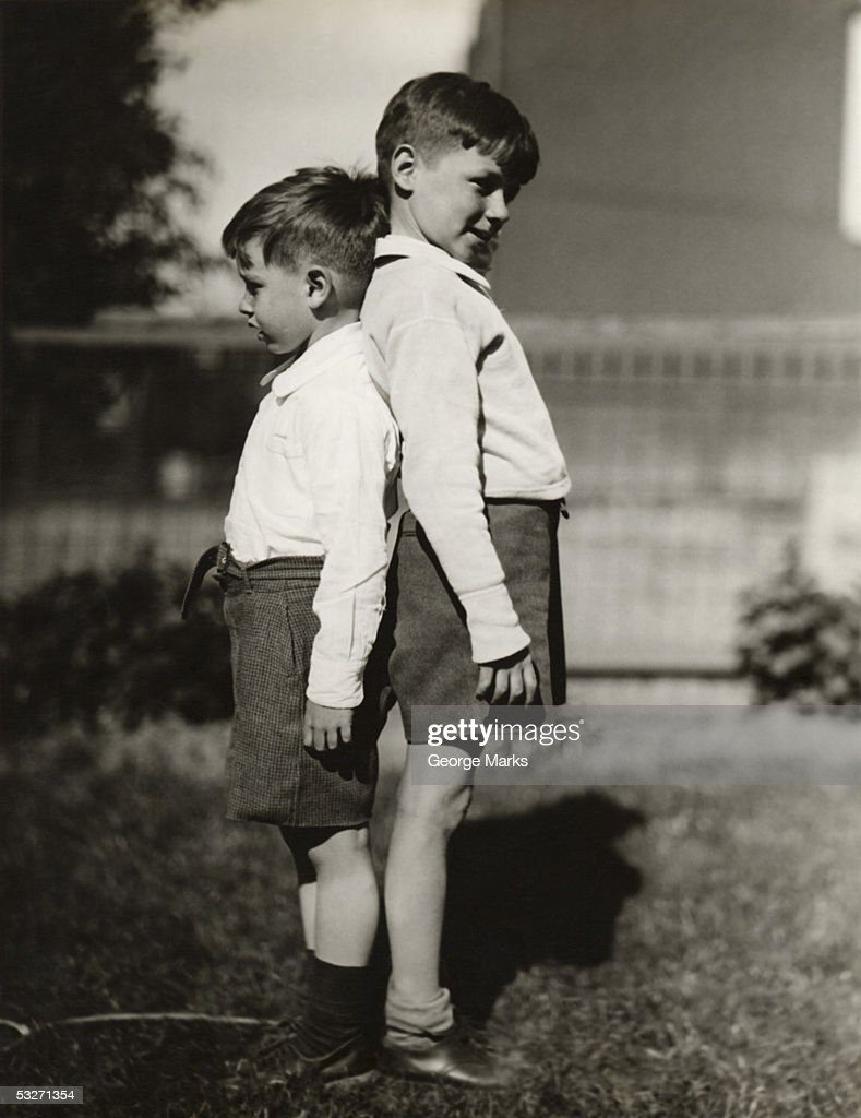 Two boys back to back comparing heights : Stock Photo