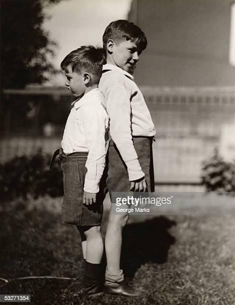 two boys back to back comparing heights - bruder stock-fotos und bilder