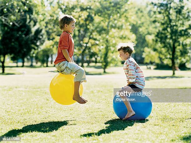 Two Boys Bouncing on Space Hoppers