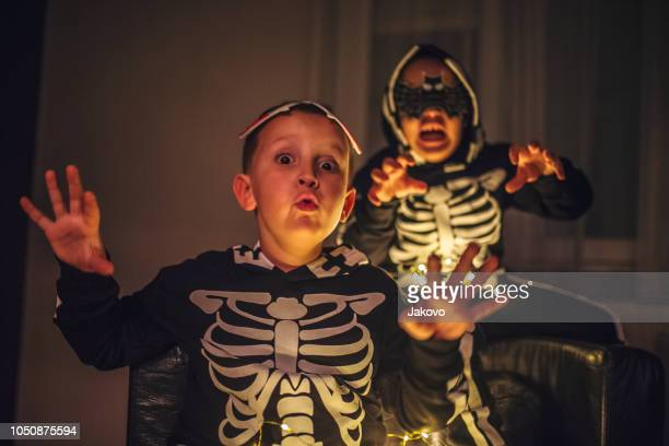 Two boys , brothers , wearing skeleton Halloween costume