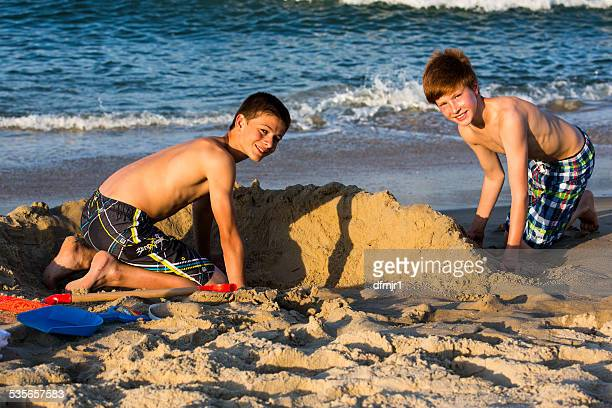 Two boys building a sand castle on the beach