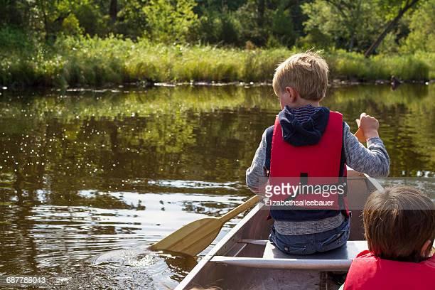 Two boys canoeing on lake