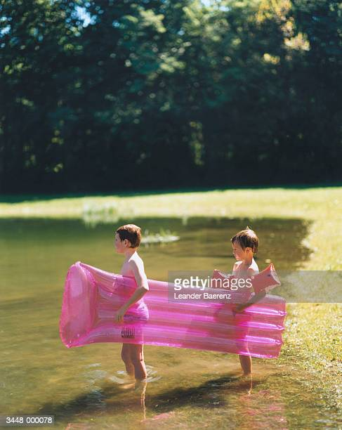 two boys carrying mattress - inflatable raft stock pictures, royalty-free photos & images