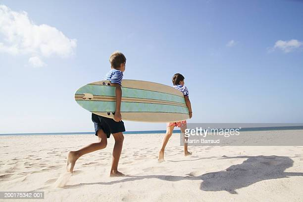 Two boys (7-9) carrying surfboard on beach, rear view