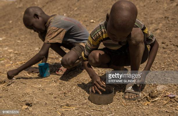 Two boys collect peas on the ground after a food distribution at the Protection of Civilian site in Bentiu South Sudan on February 13 2018 Bentiu's...