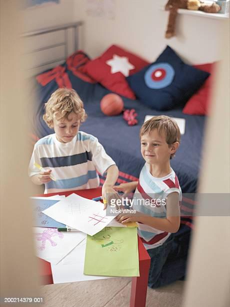 two boys (6-8) colouring in bedroom, view through doorway - colouring bildbanksfoton och bilder