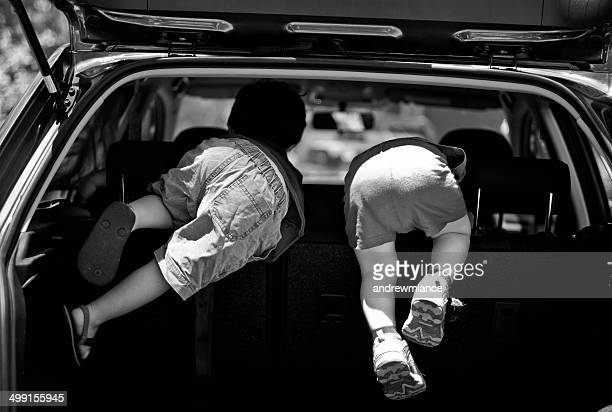 Two boys crawling into the back of a car