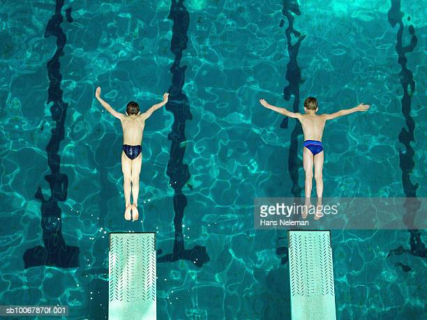 Two boys (8-9) diving off of starting block, elevated view