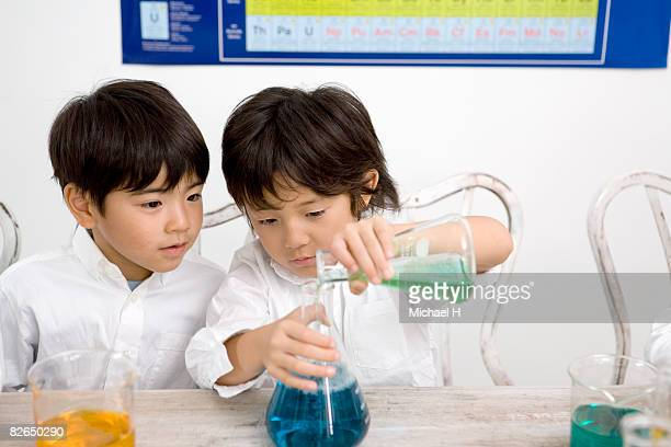 Two boys do experiment with beaker and flask