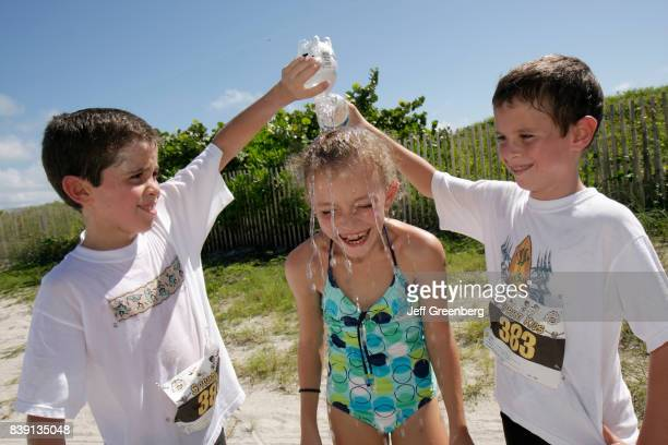 Two boys dousing a girl with water at the children's duathlon at the Publix Family Fitness Weekend event at Lummus Park