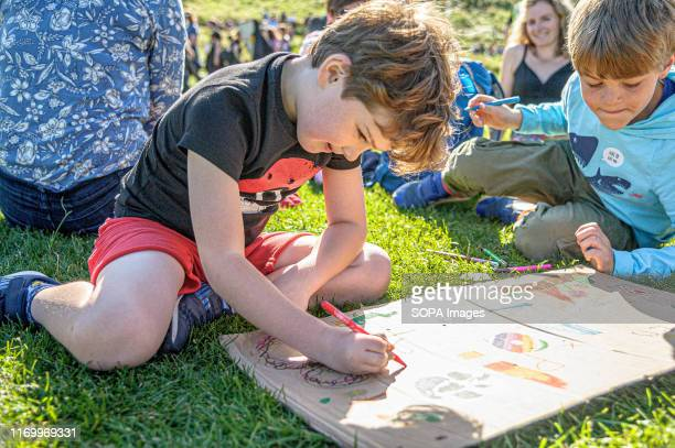 Two boys draw on a discarded placard with felt-tip pens after the march. Thousands of parents and students took part in the March through Edinburgh...
