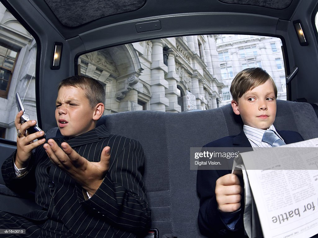 Two Boys Dressed as Businessmen in the back of a Taxi, one Reading a Newspaper the Other Looking Angry Using a Mobile Phone : Stock Photo