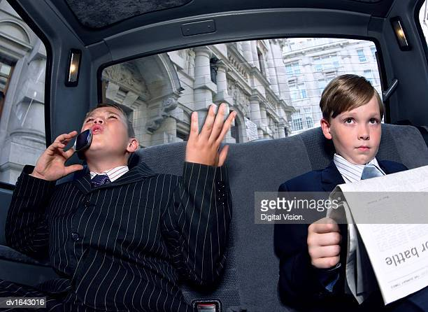 Two Boys Dressed as Businessmen in the back of a Taxi, one Reading a Newspaper the Other Gesturing Angrily and Using a Mobile Phone