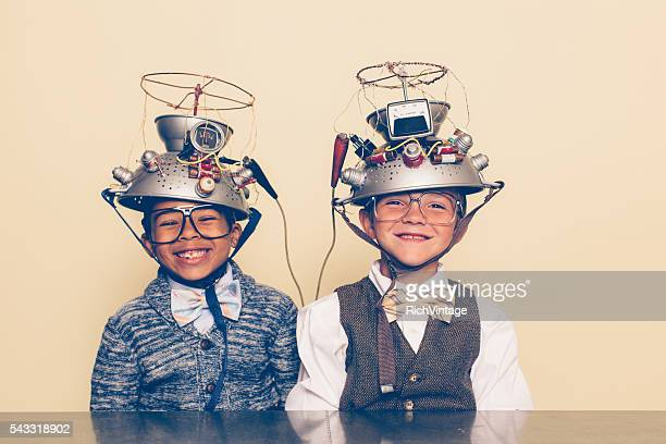 two boys dressed as nerds smiling with mind reading helmets - contraptie stockfoto's en -beelden