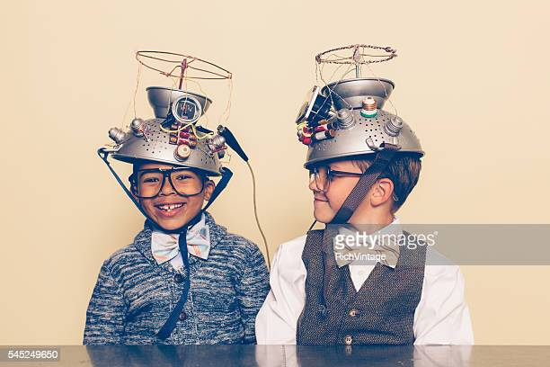 two boys dressed as nerds smiling with mind reading helmets - science and technology stock pictures, royalty-free photos & images