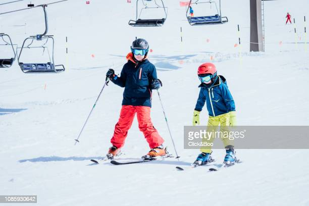 Two boys dressed in ski clothes learning to ski