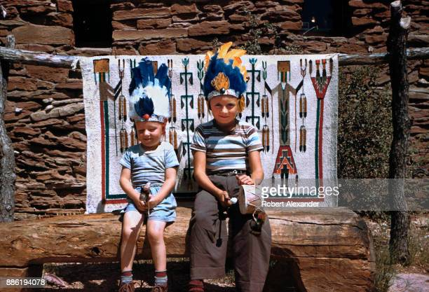 Two boys dressed in souvenir Indian headresses pose for a photo in front of a Navajo Yei pattern rug on display outside the park's Hopi House...