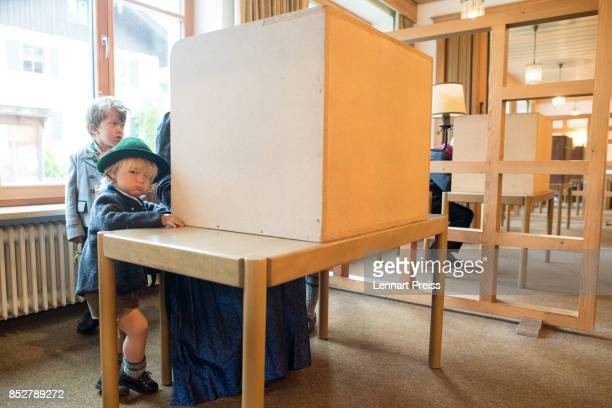 Two boys dressed in traditional Bavarian clothes wait for her mother as she fills in her election ballots at a polling station during German federal...
