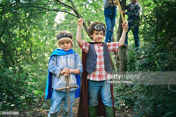 Two boys dressed up and playing in forest