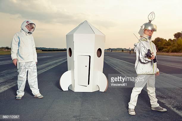 Two boys dressed up as spacemen standing at cardboard rocket