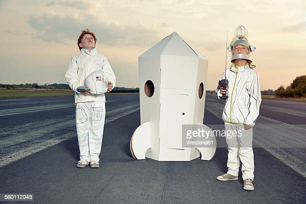Two boys dressed up as spacemen standing at cardboard rocket