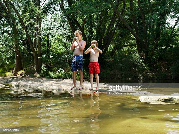 Two boys drinking water by the river