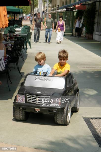 Two boys driving a ride on electric car on Lincoln Road