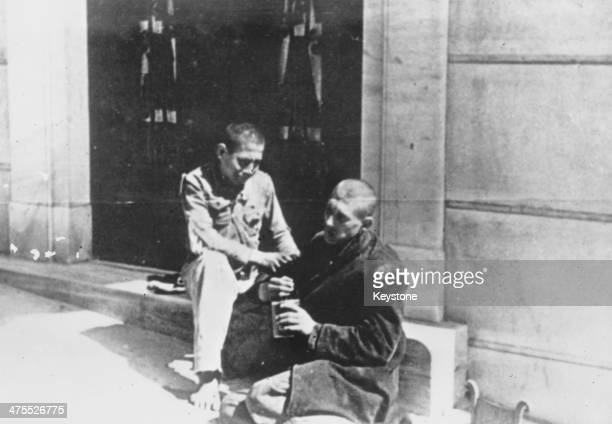Two boys eat from a discarded can they have found in an Athens street during the Great Famine, the period of mass starvation during the Axis...