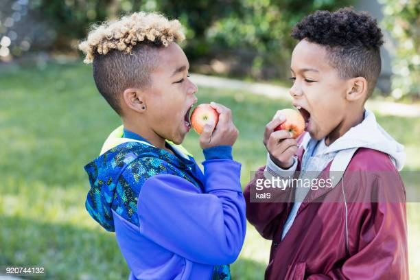 two boys eating apples - apple fruit stock pictures, royalty-free photos & images
