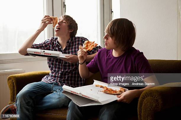 Two boys eating delivery pizza