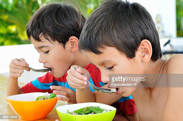Two boys (6-9) eating soup, close-up