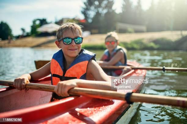 two boys enjoying kayaking on lake - life jacket stock pictures, royalty-free photos & images