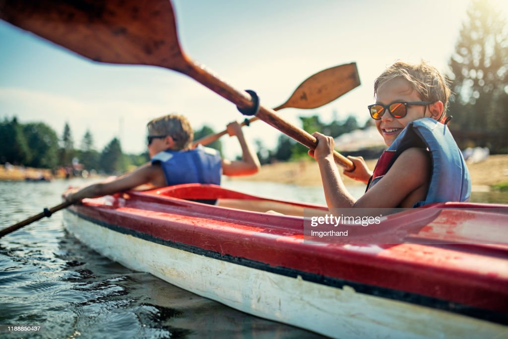 Twee jongens genieten van kajakken op het meer : Stockfoto