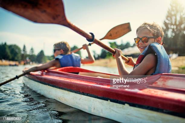 two boys enjoying kayaking on lake - summer stock pictures, royalty-free photos & images